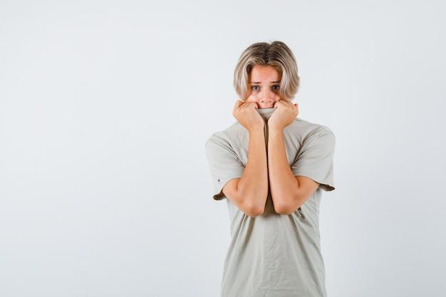 Jonge tienerjongen die kraag op gezicht in t-shirt trekt en bang kijkt. vooraanzicht.
