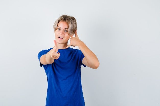 Jonge tienerjongen die laat zien bel me terug in blauw t-shirt en ziet er zelfverzekerd uit. vooraanzicht.
