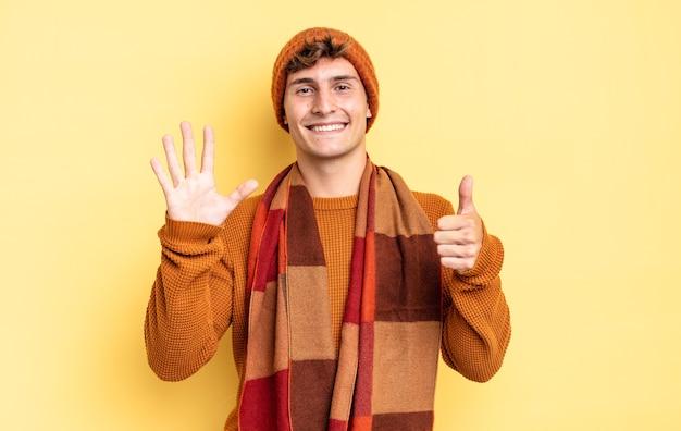 Jonge tienerjongen die lacht en er vriendelijk uitziet, nummer zes of zesde toont met de hand naar voren, aftellend