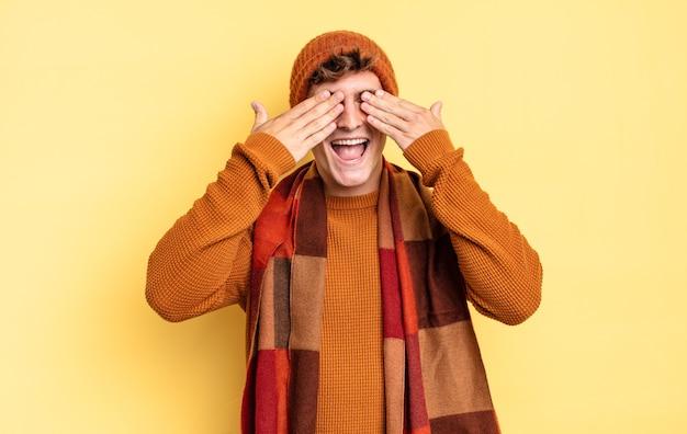 Jonge tienerjongen die lacht en zich gelukkig voelt, de ogen met beide handen bedekt en wacht op een ongelooflijke verrassing