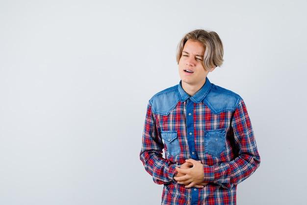 Jonge tienerjongen die last heeft van buikpijn in een geruit overhemd en er gehinderd uitziet. vooraanzicht.