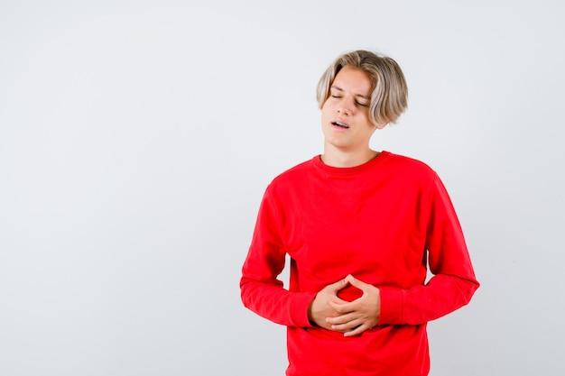 Jonge tienerjongen die last heeft van buikpijn in een rode trui en er gehinderd uitziet, vooraanzicht.