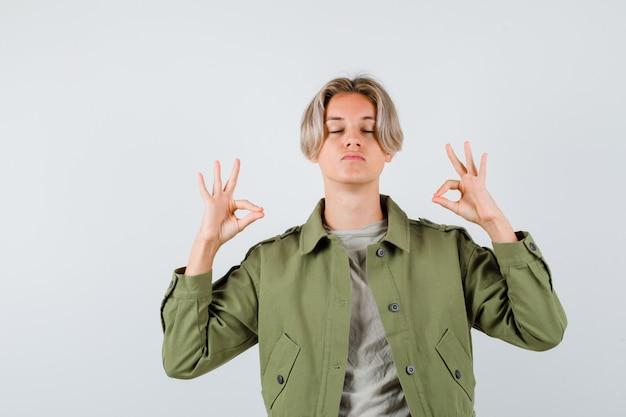 Jonge tienerjongen die mudra-teken toont, ogen dicht houdt in t-shirt, jas en er ontspannen uitziet, vooraanzicht.