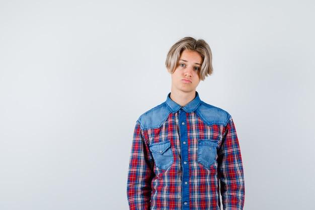 Jonge tienerjongen die naar de camera kijkt in een geruit overhemd en er teleurgesteld uitziet. vooraanzicht.