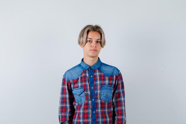 Jonge tienerjongen die naar de camera kijkt in een geruit overhemd en er verstandig uitziet. vooraanzicht.
