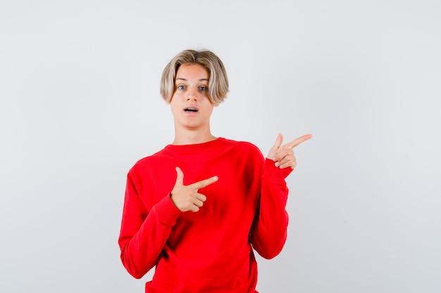 Jonge tienerjongen die naar de rechterbovenhoek in een rode trui wijst en verbaasd kijkt. vooraanzicht.