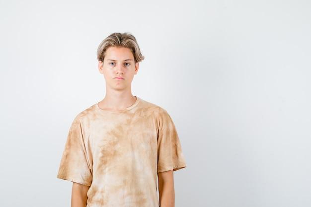 Jonge tienerjongen die naar de voorkant in een t-shirt kijkt en er boos uitziet. vooraanzicht.
