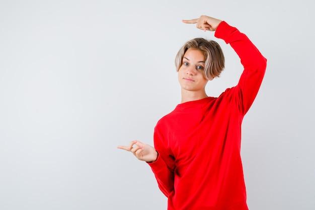 Jonge tienerjongen die naar links wijst in een rode trui en er zelfverzekerd uitziet, vooraanzicht.