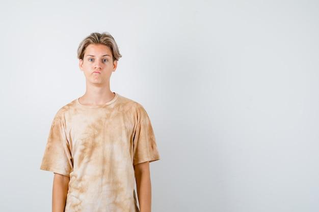Jonge tienerjongen die naar voren kijkt terwijl hij een grimas maakt in een t-shirt en er teleurgesteld uitziet. vooraanzicht.