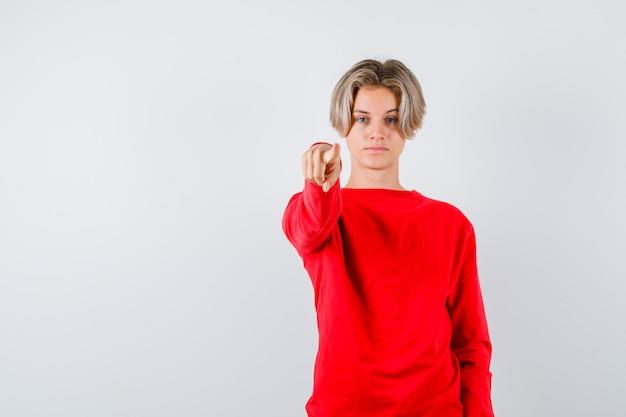 Jonge tienerjongen die naar voren wijst in een rode trui en er serieus uitziet. vooraanzicht.