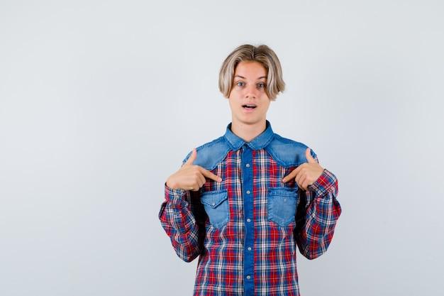 Jonge tienerjongen die naar zichzelf wijst in een geruit overhemd en er verbaasd uitziet
