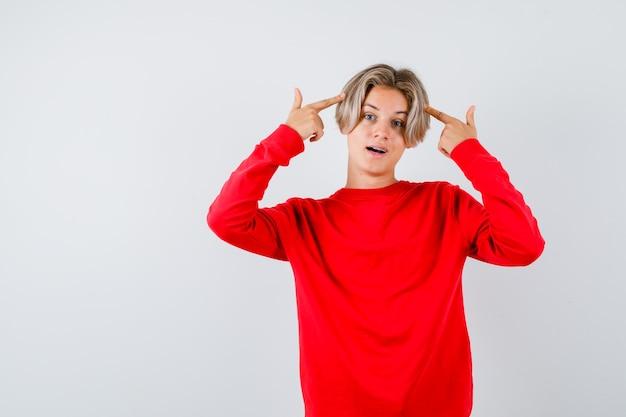 Jonge tienerjongen die naar zijn hoofd in rode trui wijst en er slim uitziet, vooraanzicht.