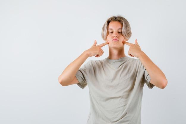 Jonge tienerjongen die naar zijn wangen wijst
