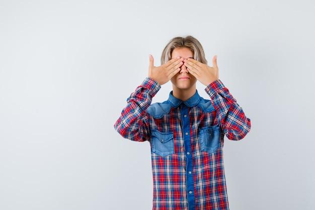 Jonge tienerjongen die ogen bedekt met handen in geruit overhemd en er bang uitziet