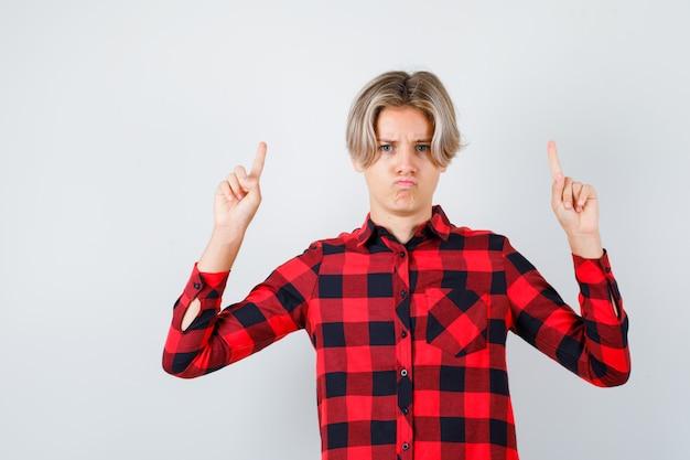 Jonge tienerjongen die omhoog wijst in een geruit overhemd en er teleurgesteld uitziet, vooraanzicht.