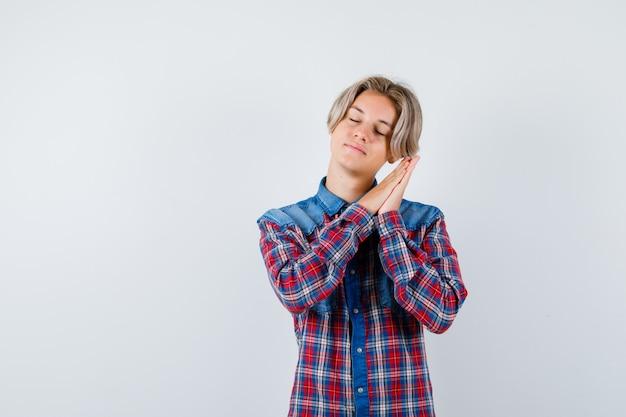 Jonge tienerjongen die op handpalmen leunt als kussen in een geruit overhemd en er slaperig uitziet. vooraanzicht.
