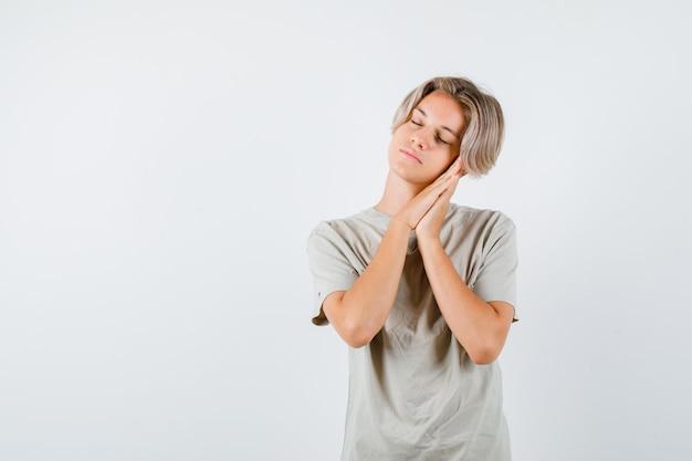 Jonge tienerjongen die op handpalmen leunt als kussen in t-shirt en er slaperig uitziet. vooraanzicht.