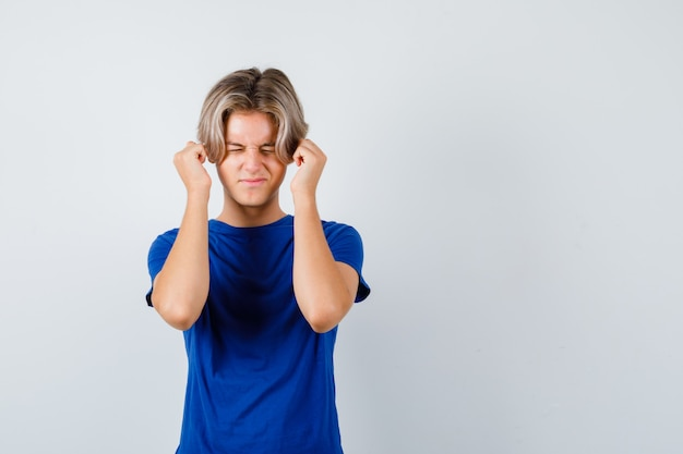 Jonge tienerjongen die oren stopt met vingers in blauw t-shirt en er bang uitziet, vooraanzicht.