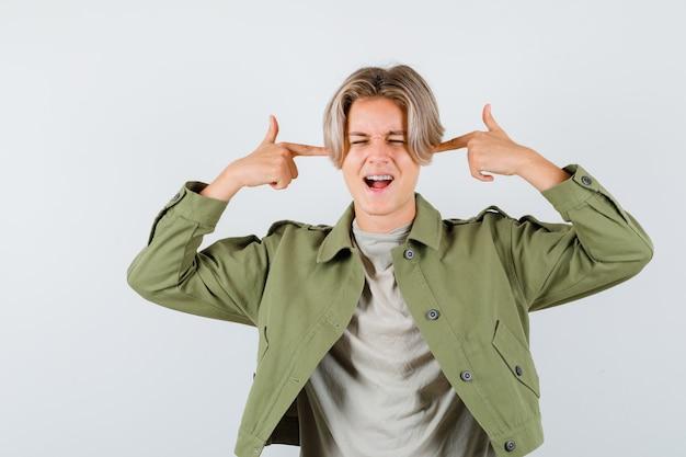 Jonge tienerjongen die oren stopt met vingers terwijl hij schreeuwt in t-shirt, jas en geïrriteerd kijkt, vooraanzicht.