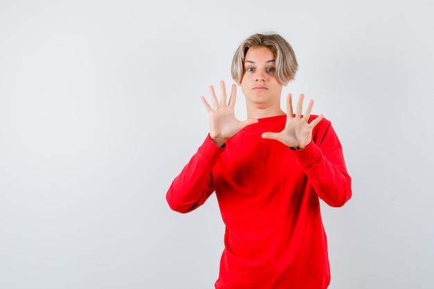 Jonge tienerjongen die overgavegebaar in rode trui toont en er bang uitziet, vooraanzicht.