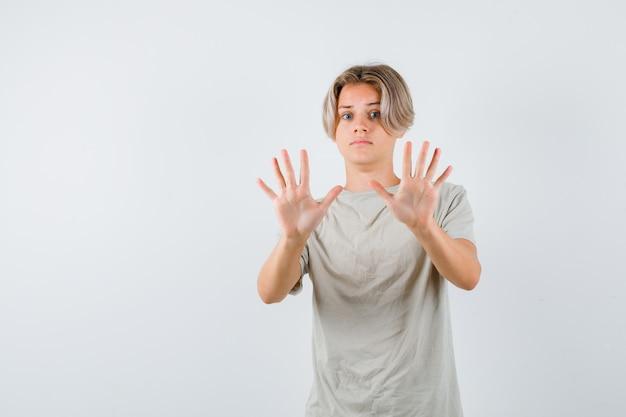 Jonge tienerjongen die overgavegebaar in t-shirt toont en bang kijkt, vooraanzicht.