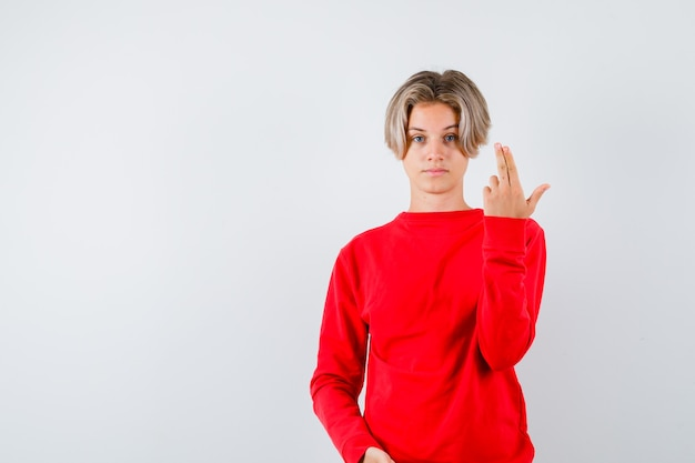 Jonge tienerjongen die pistoolgebaar in rode trui toont en er serieus uitziet, vooraanzicht.