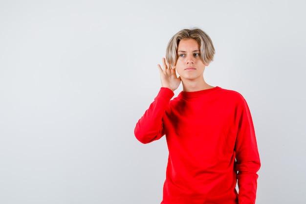 Jonge tienerjongen die privégesprek in rode sweater afluistert en verward kijkt. vooraanzicht.