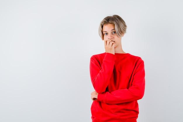 Jonge tienerjongen die spijkers in rode sweater bijt en nadenkend, vooraanzicht kijkt.