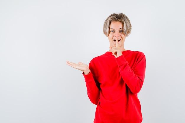 Jonge tienerjongen die stiltegebaar toont, palm opzij spreidt in rode trui en er vrolijk uitziet, vooraanzicht.