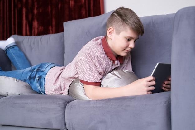 Jonge tienerjongen die tablet met behulp van die op grijze bank thuis ligt