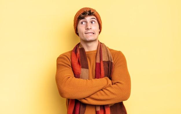 Jonge tienerjongen die twijfelt of denkt, lip bijt en zich onzeker en nerveus voelt, op zoek naar ruimte aan de zijkant