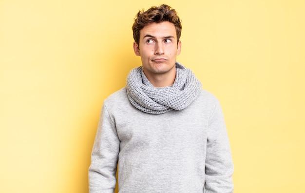 Jonge tienerjongen die verbaasd en verward kijkt, zich afvraagt of probeert een probleem op te lossen of te denken