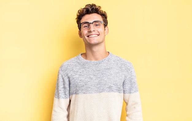 Jonge tienerjongen die vrolijk en nonchalant lacht met een positieve, gelukkige, zelfverzekerde en ontspannen uitdrukking