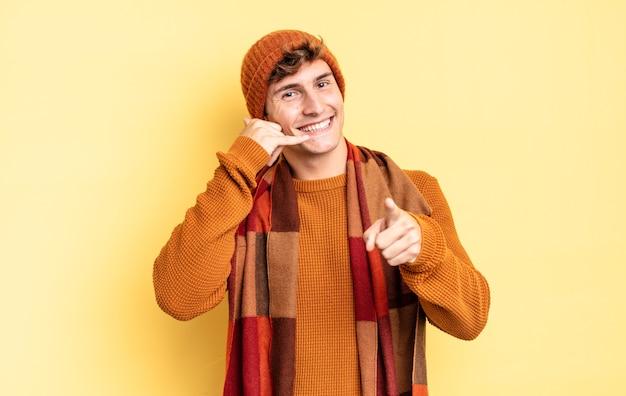 Jonge tienerjongen die vrolijk lacht en naar de camera wijst terwijl hij je later een gebaar maakt, pratend aan de telefoon