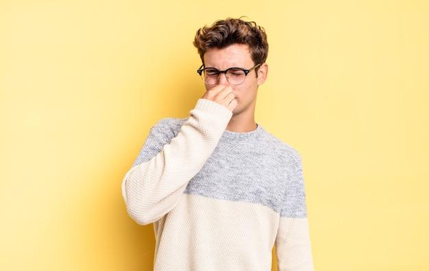 Jonge tienerjongen die walgt, zijn neus vasthoudt om te voorkomen dat hij een vieze en onaangename stank ruikt