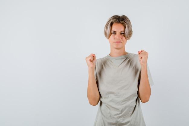 Jonge tienerjongen die winnaargebaar in t-shirt toont en gelukkig kijkt, vooraanzicht.