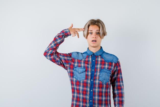 Jonge tienerjongen die zelfmoordgebaar in geruit overhemd toont en geschokt kijkt. vooraanzicht.