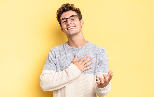 Jonge tienerjongen die zich gelukkig en verliefd voelt, glimlachend met één hand naast het hart en de andere vooraan uitgerekt