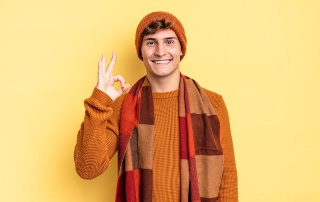 Jonge tienerjongen die zich gelukkig, ontspannen en tevreden voelt, goedkeuring toont met een goed gebaar, glimlachend