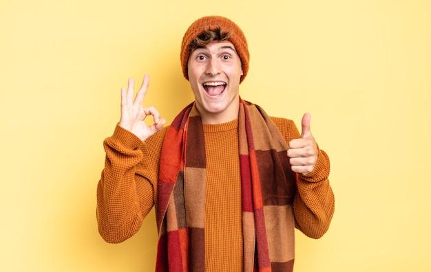 Jonge tienerjongen die zich gelukkig, verbaasd, tevreden en verrast voelt, oke toont en duimen omhoog gebaren, glimlachend