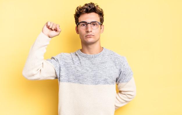 Jonge tienerjongen die zich serieus, sterk en rebels voelt, zijn vuist opheft, protesteert of vecht voor revolutie