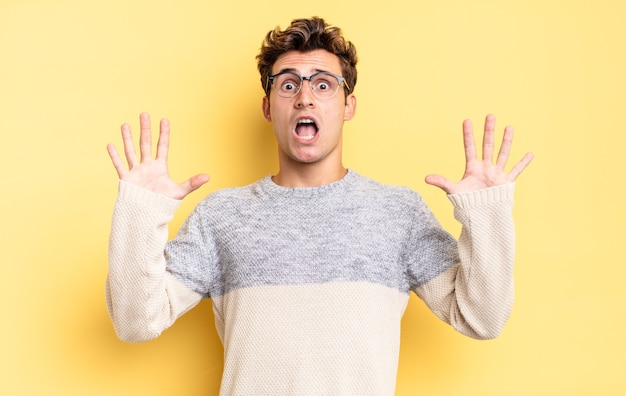 Jonge tienerjongen die zich verdoofd en bang voelt, bang is voor iets angstaanjagends, met de handen vooraan open en zegt: blijf weg