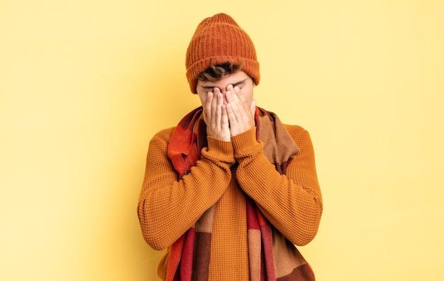 Jonge tienerjongen die zich verdrietig, gefrustreerd, nerveus en depressief voelt, zijn gezicht met beide handen bedekt, huilt