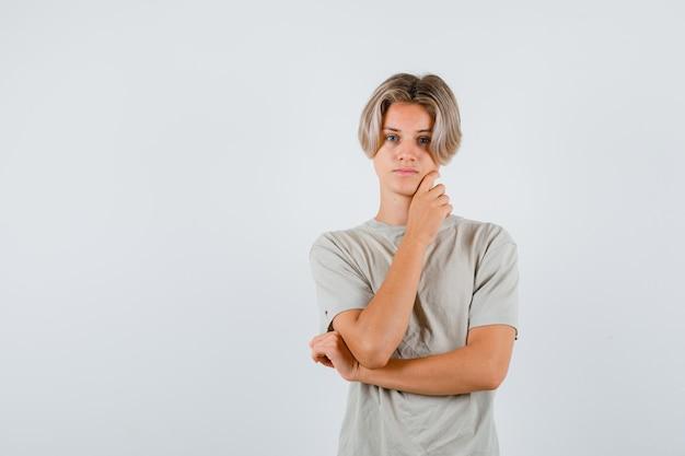 Jonge tienerjongen die zich voordeed terwijl hij zijn kaak in een t-shirt aanraakte en er verstandig uitzag. vooraanzicht.
