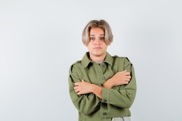 Jonge tienerjongen die zichzelf omhelst of het koud heeft in een groene jas en er verbijsterd uitziet