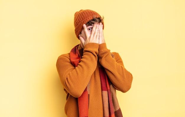 Jonge tienerjongen die zijn gezicht bedekt met handen, tussen de vingers gluurt met een verbaasde uitdrukking en naar de zijkant kijkt