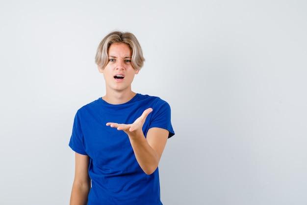 Jonge tienerjongen die zijn hand aan de voorkant in een blauw t-shirt uitrekt en perplex kijkt. vooraanzicht.