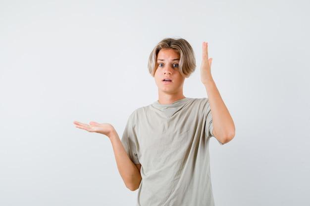 Jonge tienerjongen die zijn hand in de buurt van het hoofd houdt, de handpalm opzij spreidt in een t-shirt en er verbaasd uitziet. vooraanzicht.