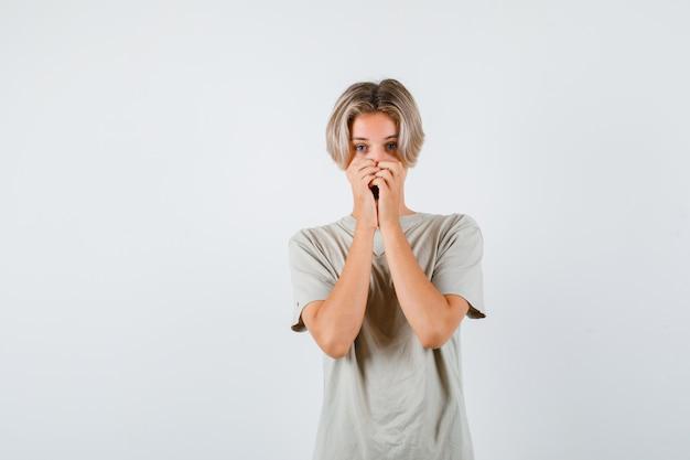 Jonge tienerjongen die zijn mond in een t-shirt houdt en er bang uitziet. vooraanzicht.