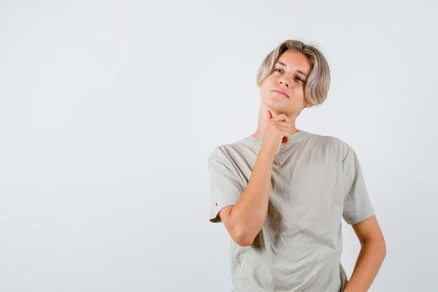 Jonge tienerjongen die zijn nek aanraakt terwijl hij wegkijkt in t-shirt en peinzend kijkt